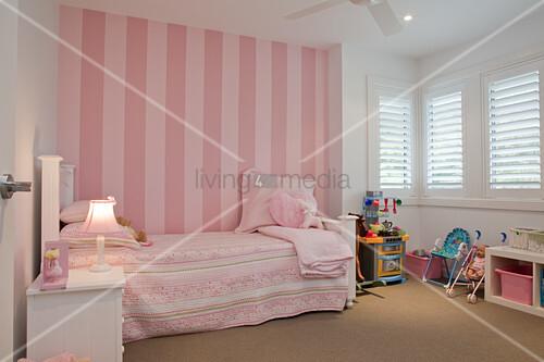 romantisches m dchenzimmer in rosa und weiss vintage bett vor gestreifter tapete in rosa an. Black Bedroom Furniture Sets. Home Design Ideas