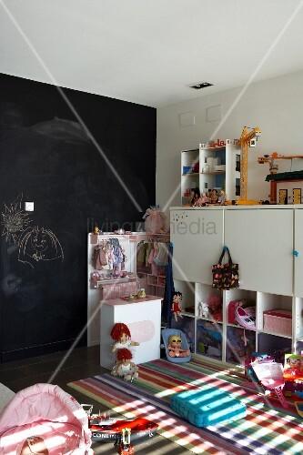 Schwarze Wand mit Kinderzeichnungen; davor weisse Kinderzimmermöbel ...
