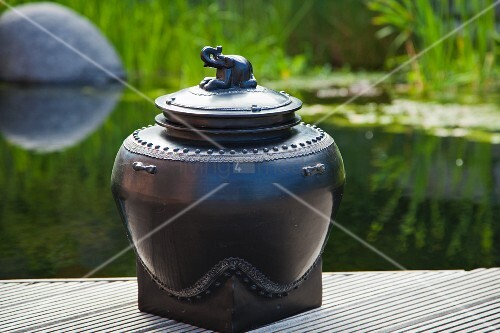 Lacquerware pot with elephant next to pond