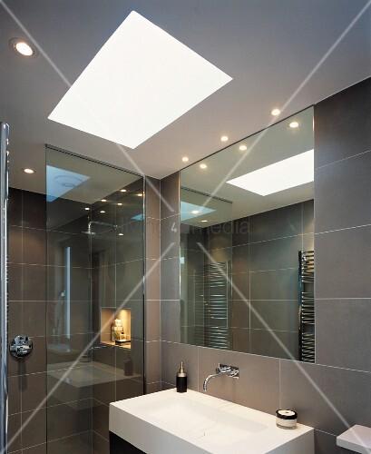 Modern, grey-tiles bathroom with skylight above designer sink