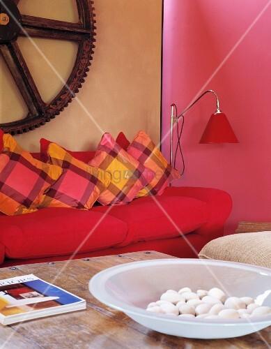 antikes zahnrad ber sofa in poppigen farben und schale mit kieseln auf antikem tisch bild. Black Bedroom Furniture Sets. Home Design Ideas