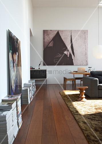 Wohnraum Mit Modernen Bildern An Der Wand Und Zeitschriftenstapel Auf  Dunklem Dielenboden