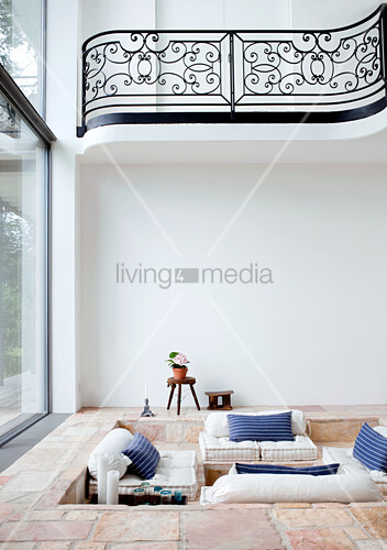 Gemütliche Sitzgrube Im Steingefliesten Fussboden Eines Wohnzimmers Mit  Fensterfront Und Galerie