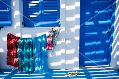 Light and shadow play on a facade of a Mediterranean home with blue window shutters and clothes hanging to dry underneath