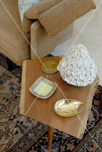 Various dishes on wooden side table in simple 50s style and partial view of sofa armrest