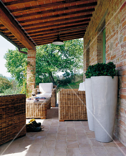 Veranda of Tuscan country house with terracotta tiles, comfortable wicker furniture and two white floor vases in foreground
