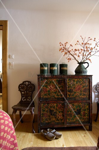 Old cans and pitcher on an antique chest of drawers (painted with flowers), next to a carved, rustic chair