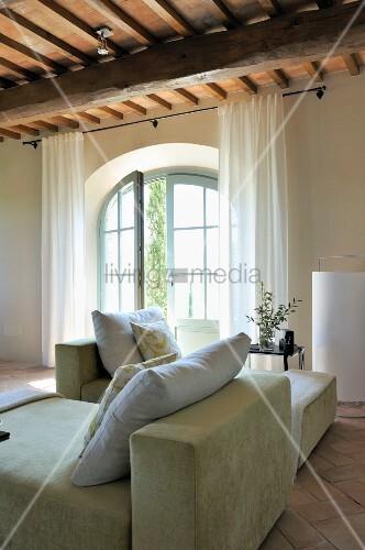 kissen auf liegesofa vor terrassent r mit rundbogen in renoviertem landhaus bild kaufen. Black Bedroom Furniture Sets. Home Design Ideas
