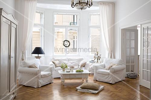 Sofagarnitur mit weissen hussen und couchtisch unter kronleuchter im wohnzimmer erker einer - Wohnzimmer kronleuchter ...