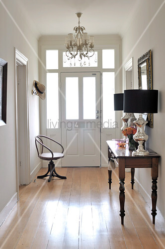 Console table and antique swivel chair in hallway of renovated country house