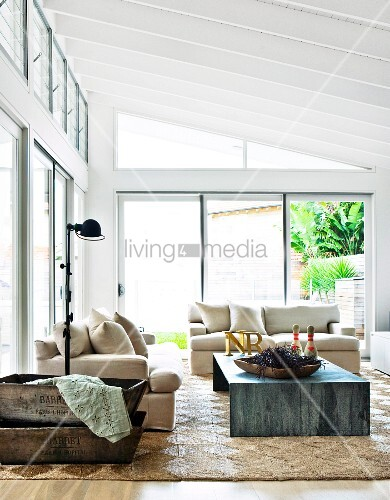 Sofa set with pale upholstery and metal table in modern living room in contemporary glass and steel extension