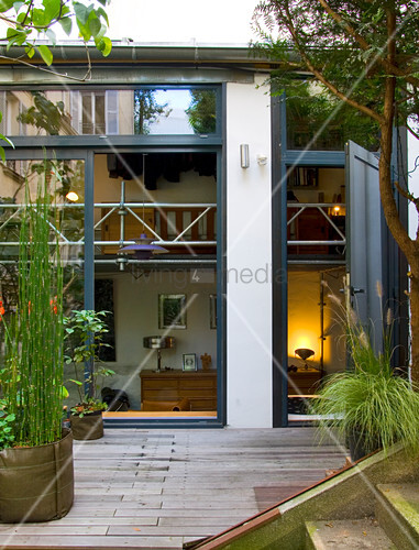 Two-room courtyard maisonette in Paris with planted deck - glazed facade open to height of gallery in split-level construction