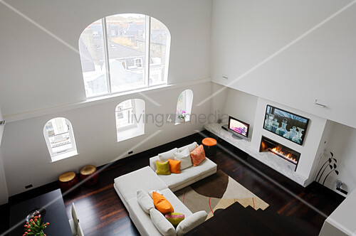 Two-storey interior of London apartment with view from above of arched window and sofa in front of gas fire