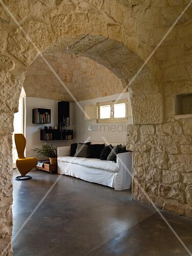 Blick durch Naturstein Rundbogen in ein Wohnzimmer in einem Trullo – Bild kaufen – living4media