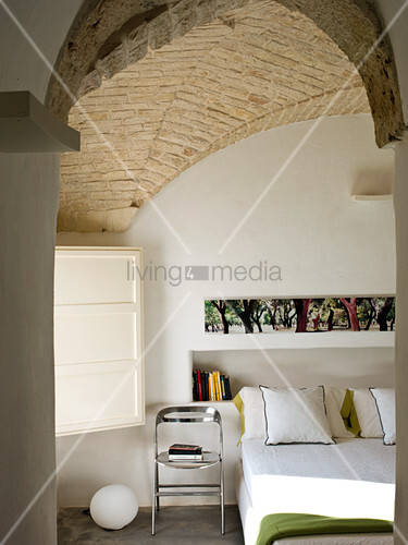 Modern metal chair next to double bed in front of books in niche in bedroom with brick vaulted ceiling