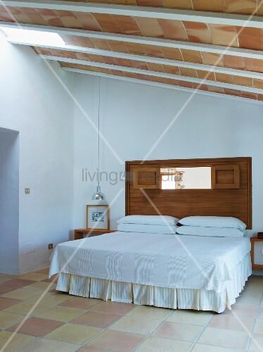 doppelbett mit husse und weisser tagesdecke in schlichtem. Black Bedroom Furniture Sets. Home Design Ideas
