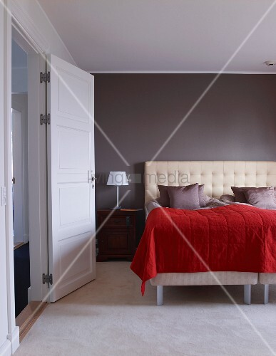 bett mit gepolstertem kopfteil und roter tagesdecke vor. Black Bedroom Furniture Sets. Home Design Ideas