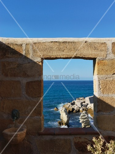 Window-like opening in stone wall with coastal view