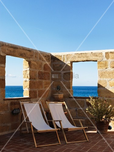 Wooden deckchairs with pale canvas seats on Mediterranean terrace surrounded by high stone wall with openings showing sea view