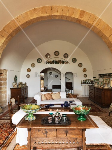 View across antique table into Mediterranean living room with barrel-vaulted ceiling and wall plates around arched doorway