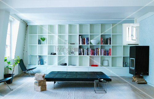 Black leather couch and white fitted shelving with square compartments