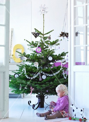 Child sitting on floor in front of decorated Christmas tree