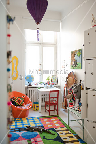 Bright child's bedroom with colourful rug and red chair at small table below window