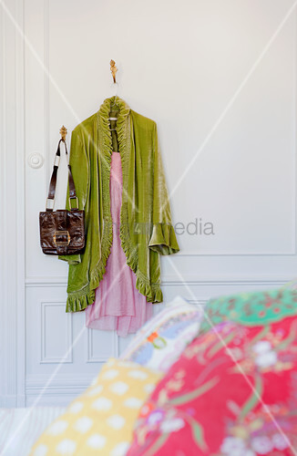 Light green dressing gown over nightdress and bag hanging from wall hooks in bedroom with traditional ambiance