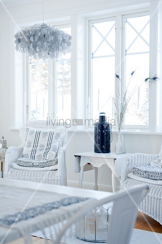 weiße Rattan Stühle mit Kissen neben Beistelltisch am Fenster eines Wohnzimmers in skandinavischem Stil