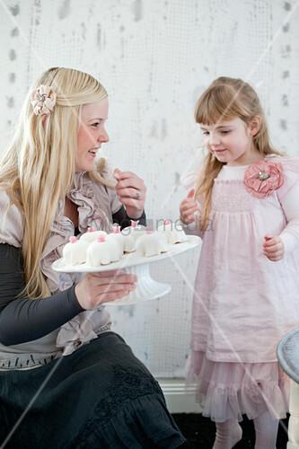 Festlich gekleidete Mutter mit kleiner Tochter eine Etagere mit Geburtstagsküchlein in der Hand haltend