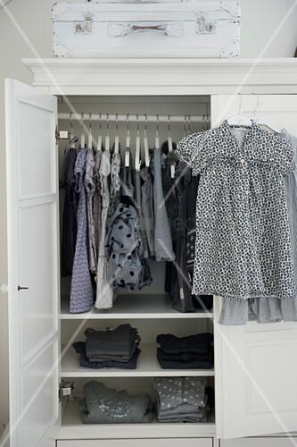 Blick in offenen Kleiderschrank auf aufgehängte Kleider und Mädchenkleider auf Bügel an Tür gehängt