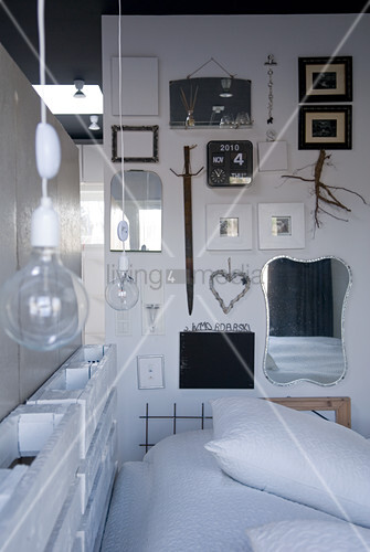 Purist bed made from pallets with light bulbs at head end; collection of frames and mirrors on side wall