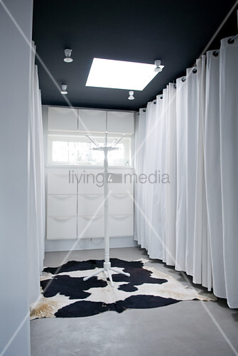Dressing room with curtained wardrobes and shoe cabinets on end wall