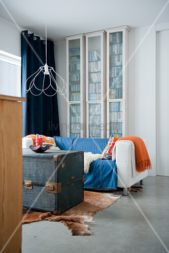 Youthful interior with skeletal lampshade above old travelling trunk and cow-skin rug on polished concrete floor