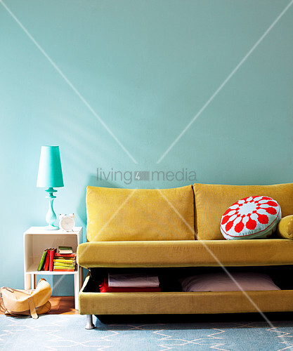 Yellow-brown sofabed with half-opened bedding box combined with table lamp and wall in complementary colours