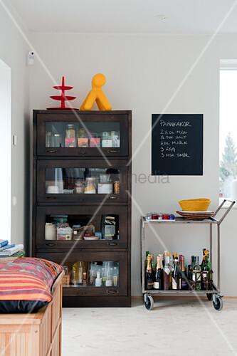 Dark wood display case next to portable bar on tea trolley in corner of modern dining room