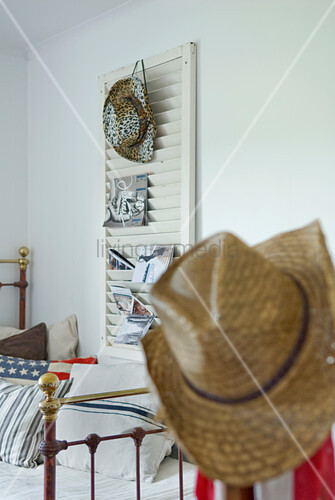 Straw hat, vintage metal bed frame and cowboy hat and magazines on louvred shutter used as rack on white bedroom wall