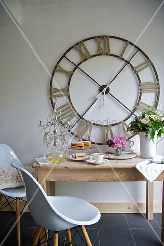 holztisch mit weissen schalenst hlen und grosse wanduhr in einer k che bild kaufen living4media. Black Bedroom Furniture Sets. Home Design Ideas