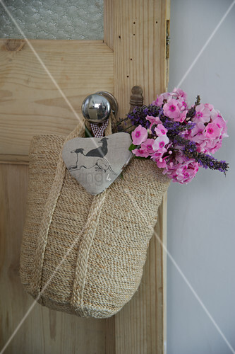 Knitted bag with posy and fabric heart hanging on door knob