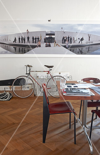 Bauhaus-style table and chair in front of large photo on wall above bicycle