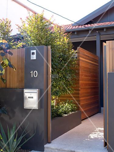 dunkelgraue gartenmauer mit offenstehender t r und blick auf sichtschutz aus holz vor wohnhaus. Black Bedroom Furniture Sets. Home Design Ideas