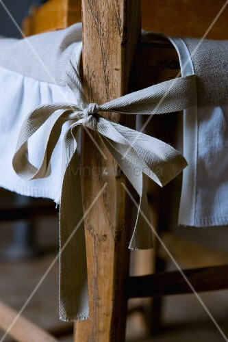 Fabric ribbon tying pale, natural linen loose cover to chair leg