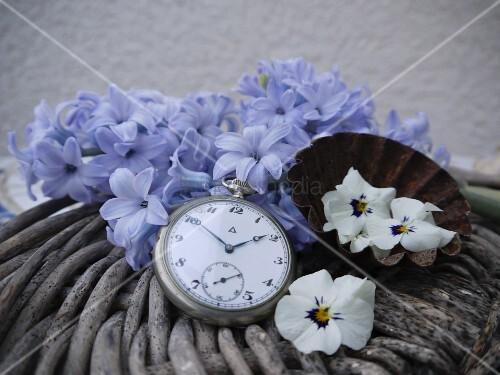 Vintage pocket watch and petals on rattan basket