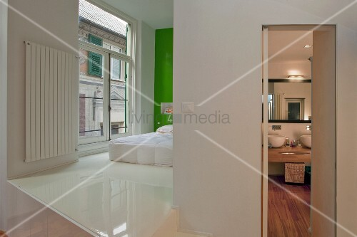 offener schlafbereich mit weissem kunstharzboden und bett vor gr n get nter wand neben bad mit. Black Bedroom Furniture Sets. Home Design Ideas