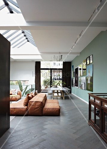 Rust-coloured floor cushions on dark herringbone floor in open-plan interior with skylight
