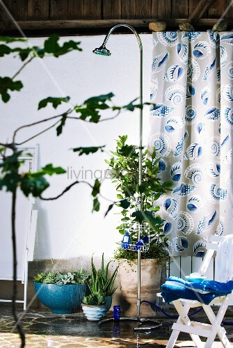 Mobile outdoor shower on terrace with potted plants and curtain with pattern of stylised shells in background