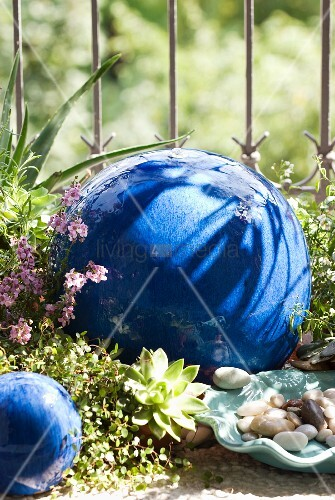Blue-glazed, ceramic, spherical water feature amongst ground cover plants and decorative pebbles against balcony railings