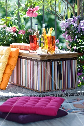 Shades of orange and purple - drinks in a summer garden with striped coolbox and cushions against flowering oleander and phlox