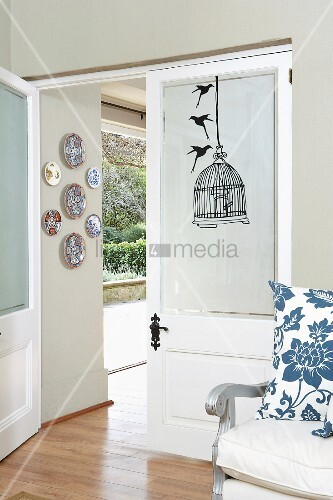 Open double doors with view into garden and partially visible armchair