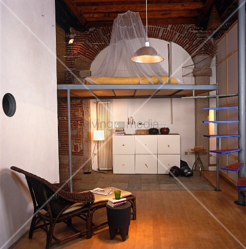 Modern living in industrial building - sleeping platform on open gallery with spiral staircase